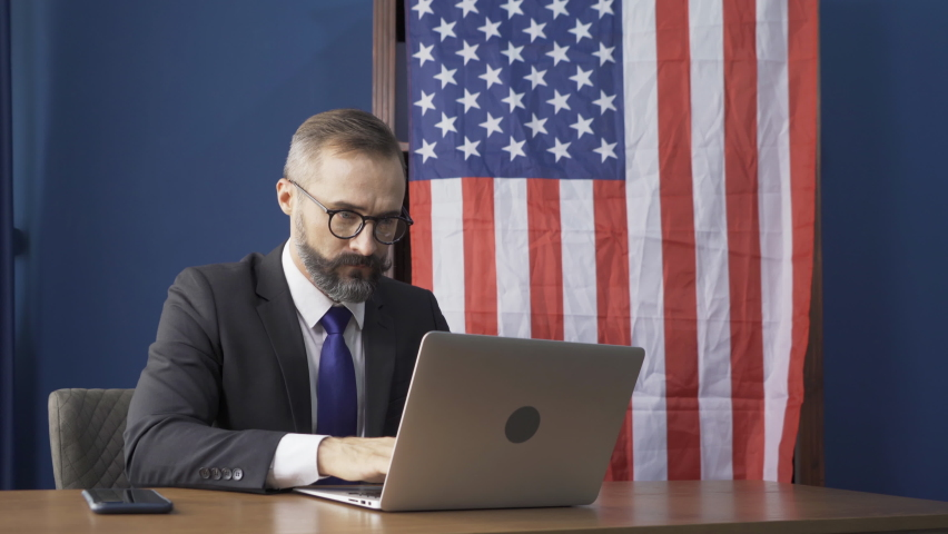 Business white vintage american man, caucasian person working from home, thinking about problem with computer notebook laptop and suffering from depression with american or usa national flag.
