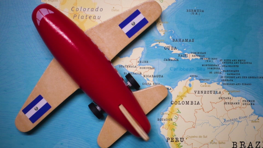 A red plane with a flag of El Salvador attached to its wings is crossing the map of El Salvador.