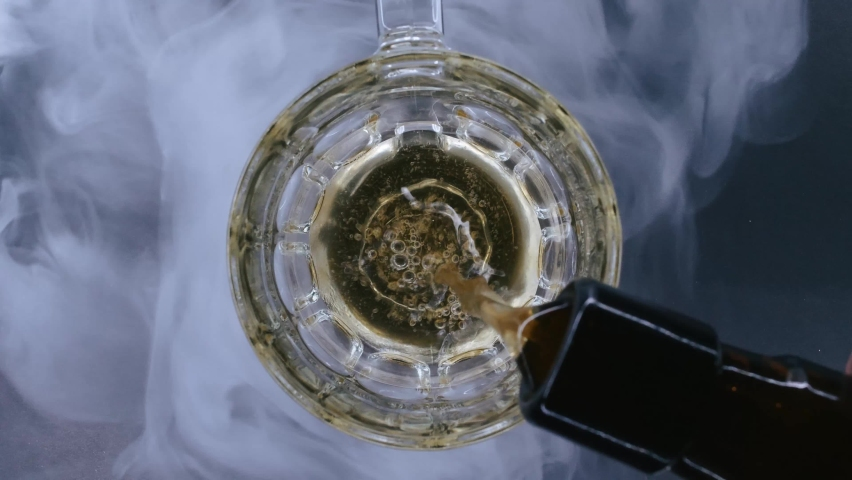 Top close up view of beer is pouring from the bottle into glass with cold smoke in background in slowmotion in 4k resolution. Cold lager beer with foam and bubbles | Shutterstock HD Video #1058910923