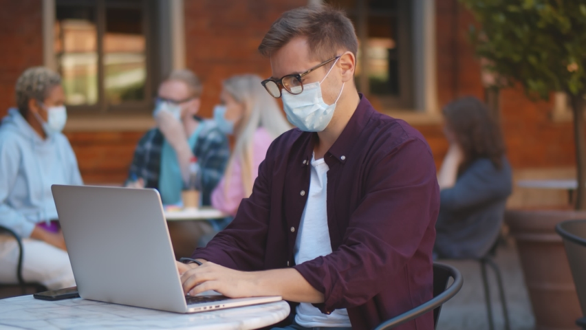 Young businessman with mask using laptop and sitting outside coffee shop. Handsome student studying on computer wearing protective mask resting at campus outdoors cafe | Shutterstock HD Video #1058912264