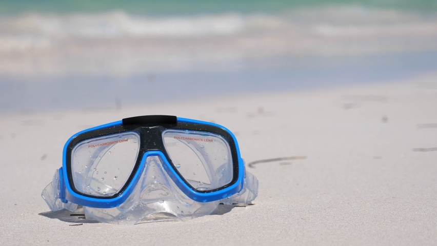 Snorkeling mask on sandy beach. Swimming tools. Nobody. Summer vacations. Travel holidays | Shutterstock HD Video #1058912717