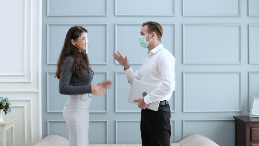 young businessman and young businesswoman in casual wear bumping elbow instead of shaking hands to keep social distance avoid touching protection COVID19 spread prevention. Discuss business project. Royalty-Free Stock Footage #1058914154
