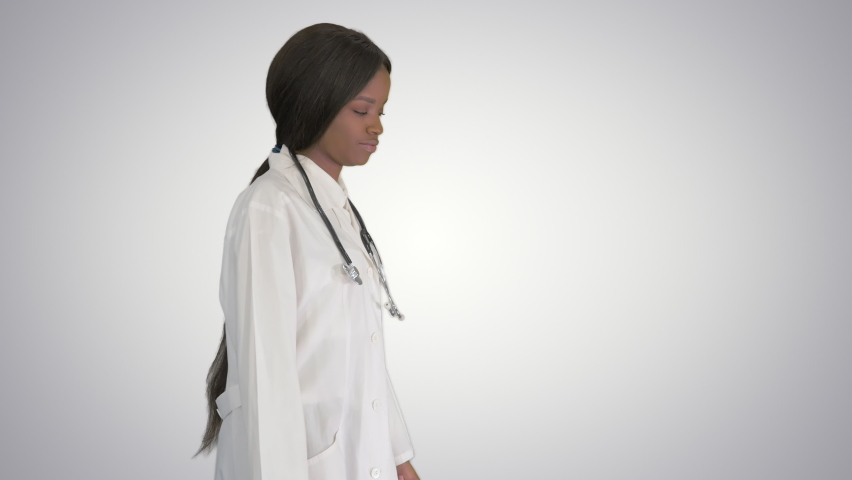 Sad African american female doctor walking with hands in her pockets on gradient background.