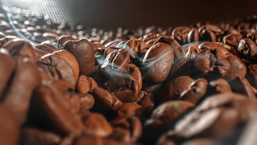 Close up of seeds of coffee. Fragrant coffee beans are roasted smoke comes from coffee beans. Royalty-Free Stock Footage #1058926358