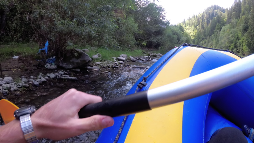 Rafting in the First Person on a Rough Mountain River. Extreme POV of the paddle and boat in motion. White Water Rafting on Rough Water. People Descending Raging Rapids from Whitewater. Chest View. | Shutterstock HD Video #1058936357