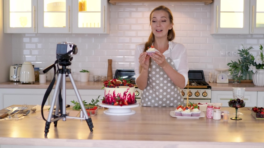Blogger pastry chef makes a video lesson about cooking a cake. young woman in an apron at home in the kitchen tells the recipe on camera. Online broadcast, author leads a blog or course about cooking. Royalty-Free Stock Footage #1058943401