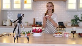 Blogger pastry chef makes a video lesson about cooking a cake. young woman in an apron at home in the kitchen tells the recipe on camera. Online broadcast, author leads a blog or course about cooking.