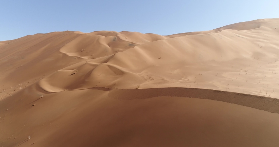 aerial dolly in shot from the formation of sand dunes in dasht e lut or sahara desert, aerial closeup shot from sand dunes, aerial pedestal up from sand dunes in desert Royalty-Free Stock Footage #1058943569