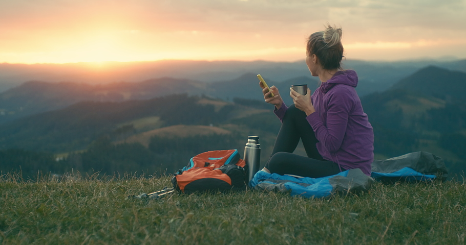 Woman hiker, hiking backpacker traveler camper with her phone camera on the top of mountain in sunny day under sun light. Beautiful mountain landscape view. Hiking, backpacking. 4K slow motion video Royalty-Free Stock Footage #1058943752
