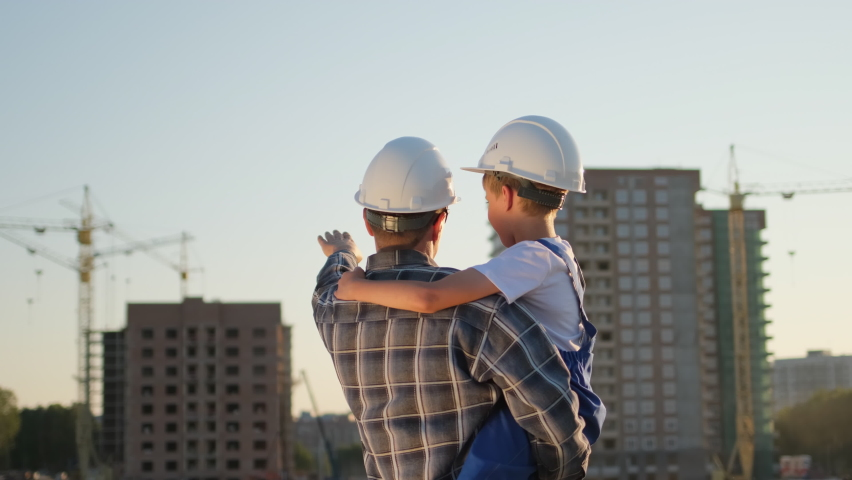 Father and son happy Family concept. Little boy and his dad engineer builder architect with safety helmets, on background new buildings and construction cranes on site. Future profession, 4 K slow-mo