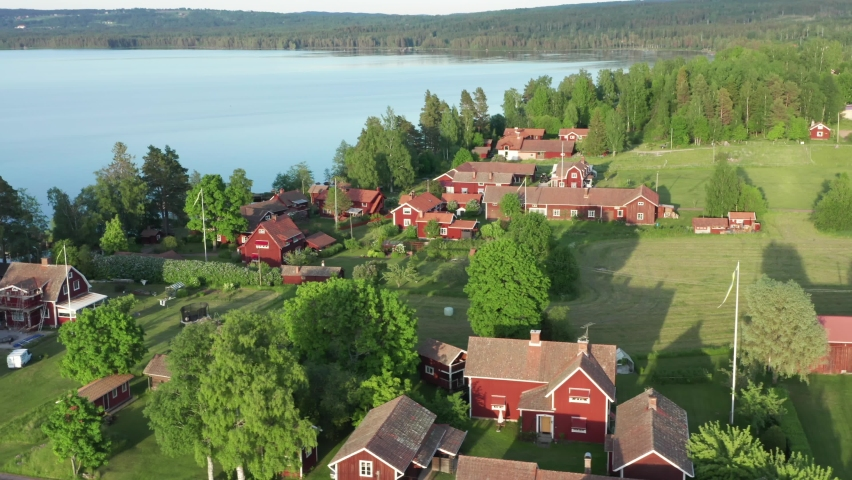 Swedish village red house drone shot. Aerial view of lake and typical wooden cabins. Sunset evening light by calm water on warm beautiful summer day. Dalarna historical province in central Sweden. Royalty-Free Stock Footage #1058946401