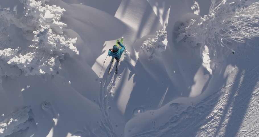 Aerial: Ski touring man crossing over the camera view. Ski touring in the mountains in winter season fresh snow. guy of ski touring on skin uphill in a line. Powder day. ski vacation travel concept