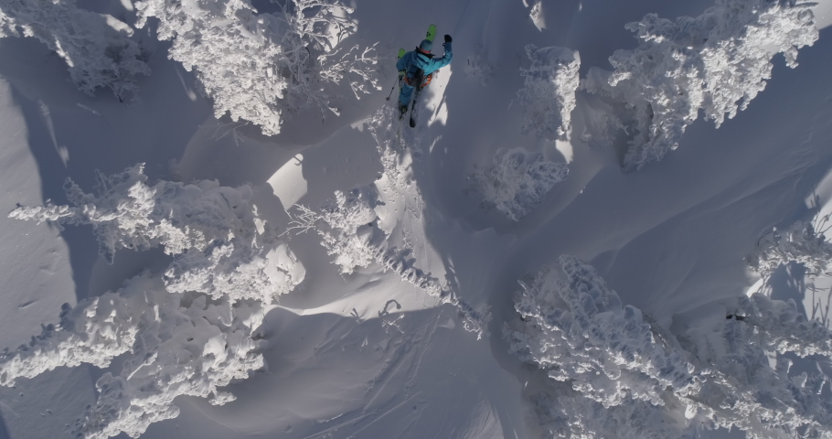 Aerial Top View: Ski touring man walks on the skis during snowfall in snow covered landscape, slow motion. 4k RAW footage. Mountain Ski Touring in Winter Storm, Epic shot,   Cross country skier.