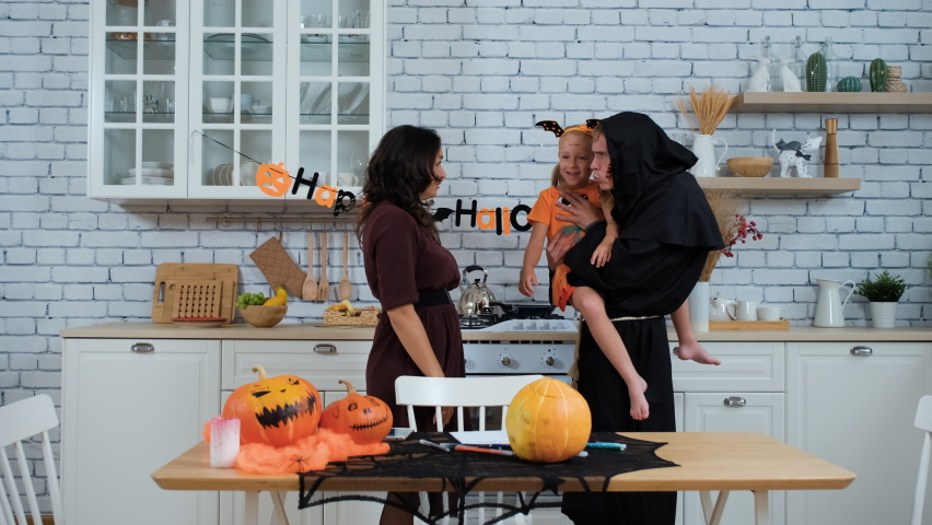 Family of Three in Costumes and Scary Makeup Having Fun in Halloween in the Kitchen. Slow Motion. People and Halloween Holiday Celebration Concept | Shutterstock HD Video #1058954615