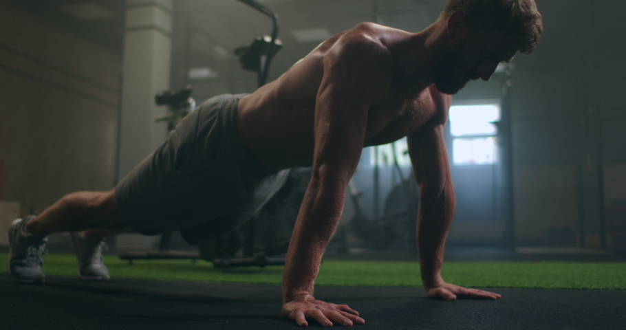 Man doing push ups in a gym. Exhaling and inhaling after push-ups and exercise. Perfect for fitness and workout. Young sports man performs pushups in the gym. The athlete is engaged in fitnes Royalty-Free Stock Footage #1058961749