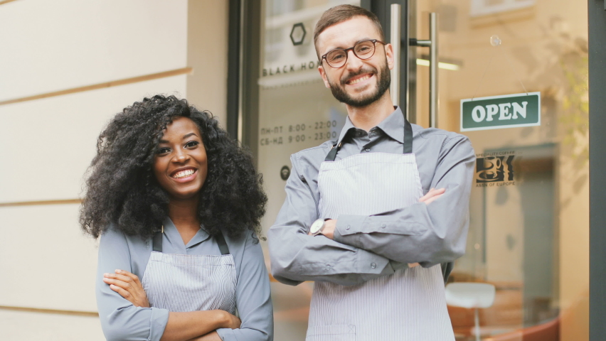Caucasian barista man and african american barista woman standing at entrance to coffee shop. Beautiful people in aprons and gray shirts standing outside and smiling with their arms crossed. Royalty-Free Stock Footage #1058963699