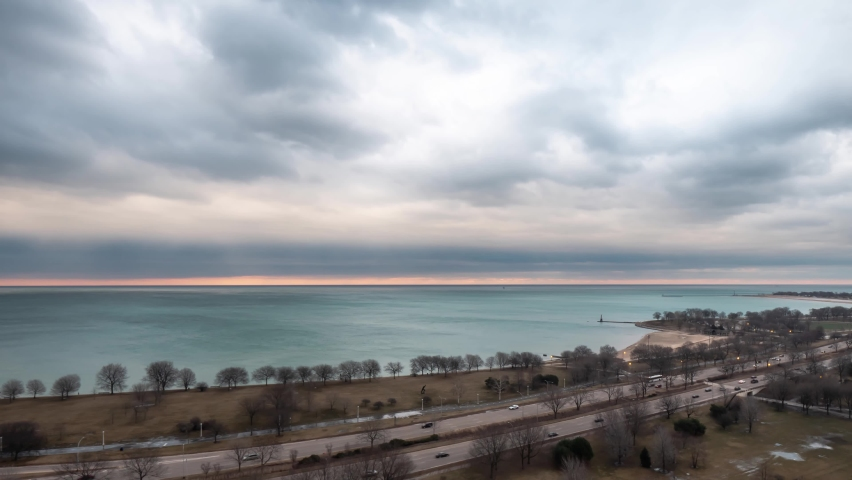 Chicago, IL - March 14th, 2019: Heavy fluffy white and blue clouds float over the water of Lake Michigan and the vehicular traffic of a busy Lake Shore Drive on the North side of the city at sunrise.