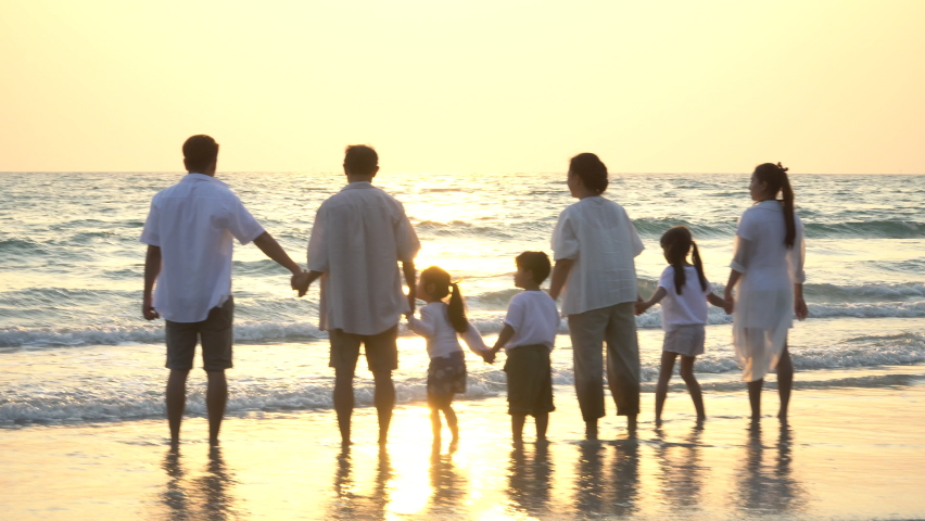 Group of asian multi generation family running on beach silhouette in sunset or Sunrise on vacation in thailand