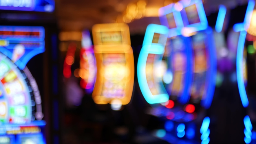 Defocused slot machines glow in casino on fabulous Las Vegas Strip, USA. Blurred gambling jackpot slots in hotel near Fremont street. Illuminated neon fruit machine for risk money playing and betting. | Shutterstock HD Video #1058969453
