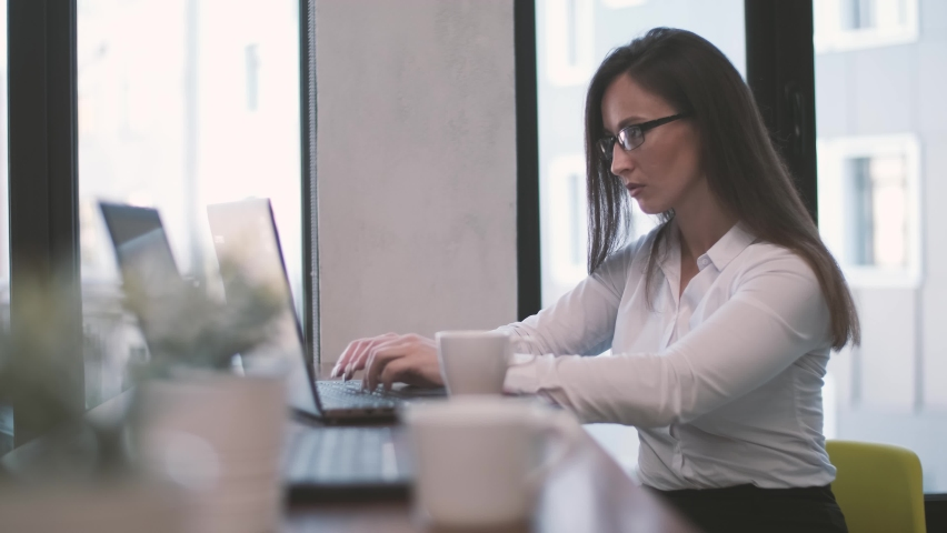 Thoughtful business woman working on a laptop computer, looking away anxiously, solving problems with a creative approach seeking inspiration. Royalty-Free Stock Footage #1058972678