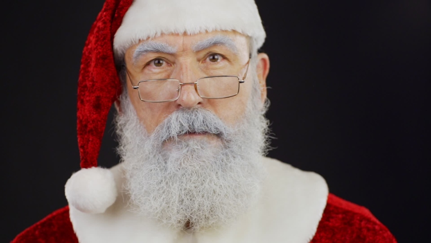 Closeup of Santa Claus looking around listening to sounds and doing shh gesture putting index finger on his lips in slow motion, then smiling and raising eyebrows against black background | Shutterstock HD Video #1058972903