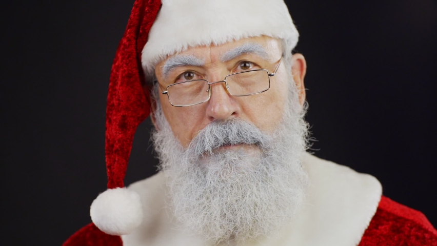 Closeup of Santa Claus looking around listening to sounds and doing shh gesture putting index finger on his lips in slow motion standing against black background | Shutterstock HD Video #1058973587