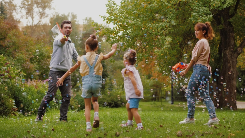 Happy parents and kids having fun together with soap bubbles in summer park. Lovely mother and father making lot of bubbles, children trying to catch bubbles flying in air, family playing outdoors