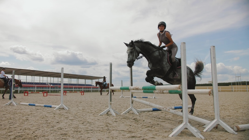 Competitive woman rider on horse jumping over obstacles, slow motion 180 fps. Gray horse leaping fence on sandy parkour riding arena, equestrian competition outdoors. Training jumping hurdle.