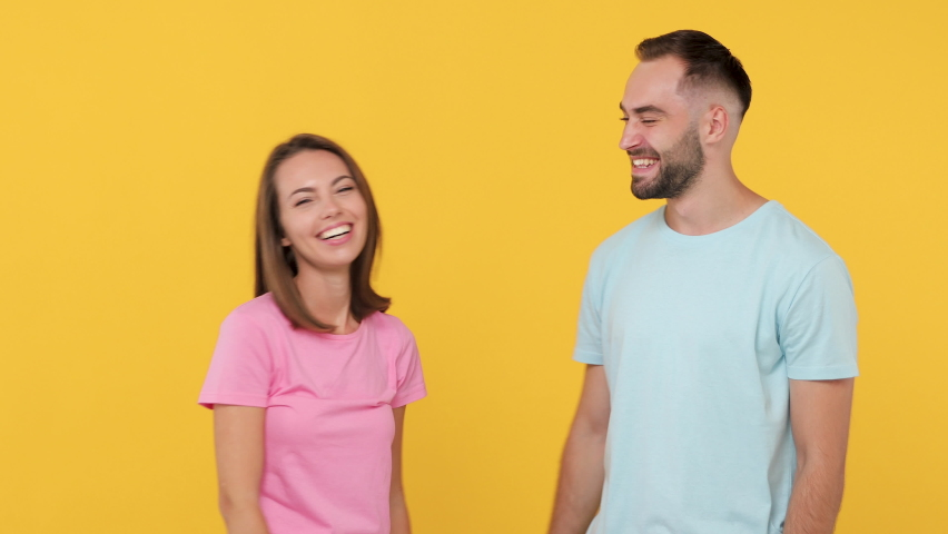 Young fun couple friends bearded man woman 20s in casual clothes posing isolated on yellow background studio. People emotions lifestyle concept Meeting together greeting hands hugging embrace gesture