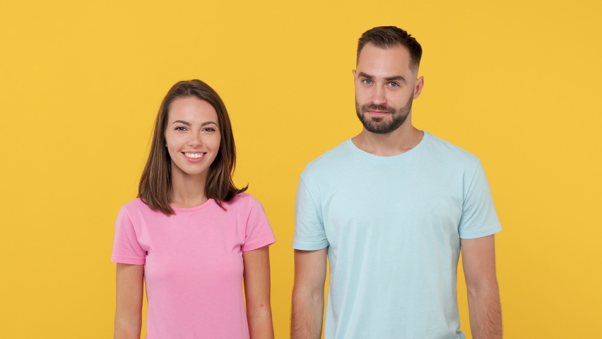 Young secret couple friends woman man 20s in basic t-shirts isolated on yellow background studio. People emotion lifestyle concept. Looking camera saying hush be quiet with finger on lips shhh gesture | Shutterstock HD Video #1058980397