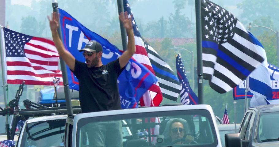 LOS ANGELES, CALIFORNIA, USA - SEPTEMBER 13, 2020: President Donald Trump supporter war veteran patriot in car with American flags driving at rally in Los Angeles, California, 4K
