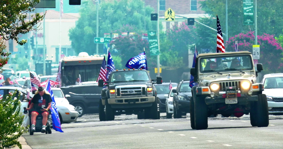 LOS ANGELES, CALIFORNIA, USA - SEPTEMBER 13, 2020: President Donald Trump supporter war veteran patriot in a wheelchair and cars with American flags driving at rally in Los Angeles, California, 4K