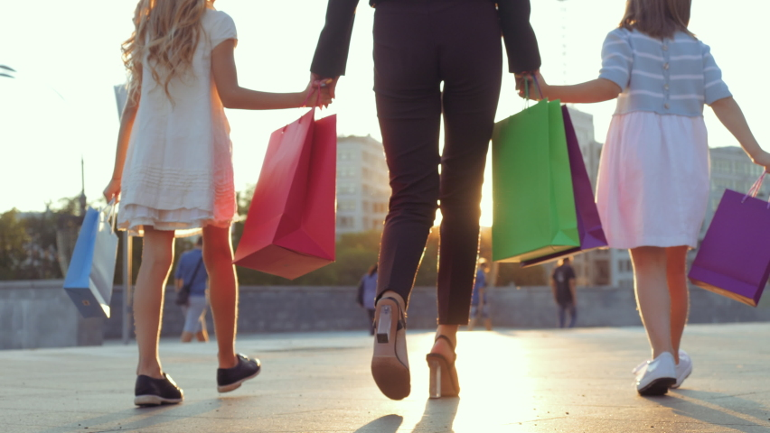Close up of human legs, two small girls walking down street in stylish shoes, holding mom's hand. Mother in fashionable luxury heels goes with daughters from shopping store, carries in packages gifts