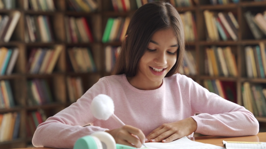 Happy smiling indian latin preteen school girl pupil studying at home sitting at desk with mom, teacher, tutor helping smart hispanic kid primary student writing doing homework, learning at table. Royalty-Free Stock Footage #1058989064