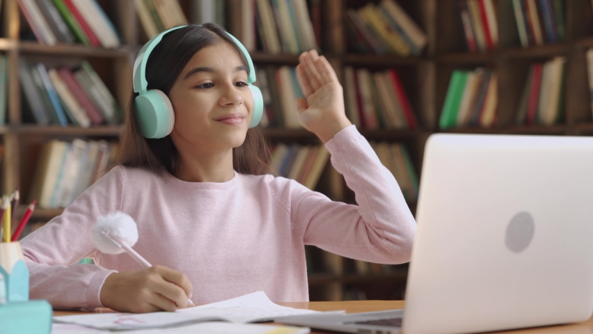 Happy indian latin preteen girl school pupil wearing headphones raising hand distance learning online at virtual lesson class with teacher tutor on laptop by video conference call studying at home. Royalty-Free Stock Footage #1058989073