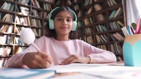 Cute indian latin preteen girl school kid child pupil wearing headphones raising hand distance learning online talking to camera at virtual lesson class by video conference call at home, webcam view.