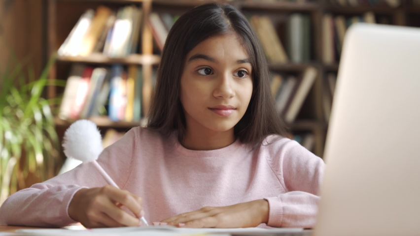 Happy indian latin girl school pupil distance learning, studying online at virtual class with teacher tutor by video conference call, watching tv lesson on laptop computer at home, in classroom. Royalty-Free Stock Footage #1058989082