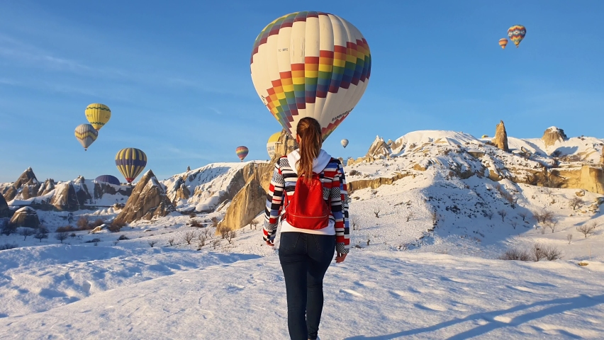 Woman rising her hands and looking on flight hot air balloons in Cappadocia Royalty-Free Stock Footage #1058989262