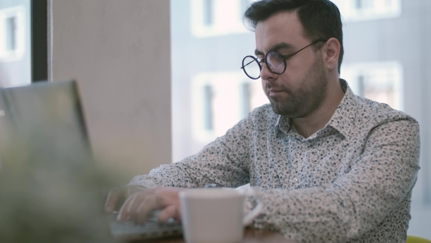 Businessman working on a laptop remotely, taking a sip of coffee, continuing to create new ideas. Royalty-Free Stock Footage #1058994749