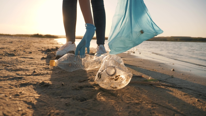 Teamwork cleaning plastic on the beach. Volunteers collect trash in a trash bag. Plastic pollution and environmental problem concept. Voluntary cleaning of nature from plastic. Greening the planet Royalty-Free Stock Footage #1058994818