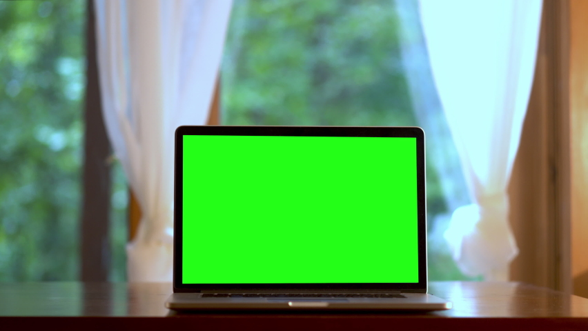 Fast dolly push in to laptop computer with green screen on a table in front of windows with curtains. Concept for remote virtual distance learning Royalty-Free Stock Footage #1058994875