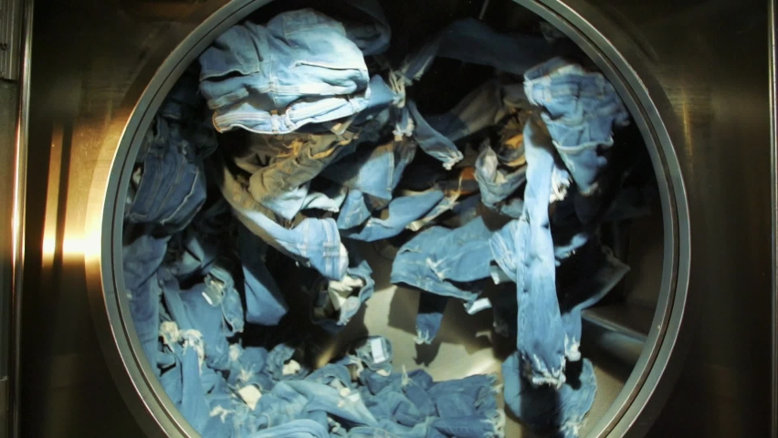 Slow motion shot of blue jeans spinning inside an industrial washer dryer in jeans factory. Royalty-Free Stock Footage #1058998514