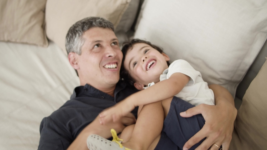 Joyful dad cuddling and tickling laughing little son on couch in living room. Boy and his father roping and playing together. Family fun time concept