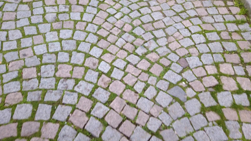 Moving on stone paving road in old city. Walkway with cobblestones, rectangular and quarried stone. Roman road. Royalty-Free Stock Footage #1059006032