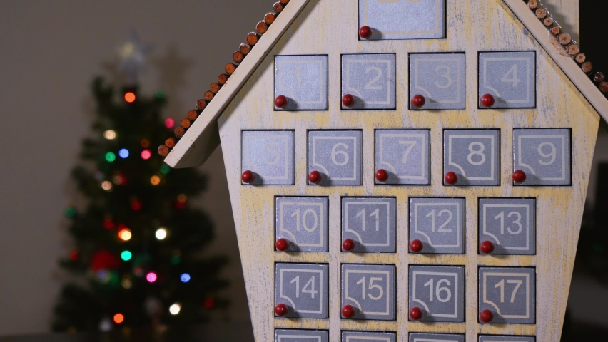 Close up shot of a hand getting candy out of a wooden Advent Calender in front of a Christmas Tree