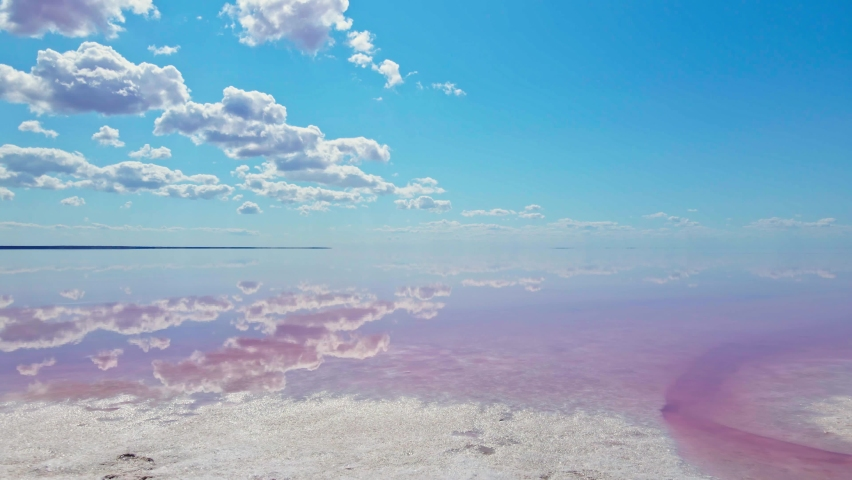 Epic drone flight over beautiful pink salt lake and clouds reflection on calm water surface | Shutterstock HD Video #1059011090