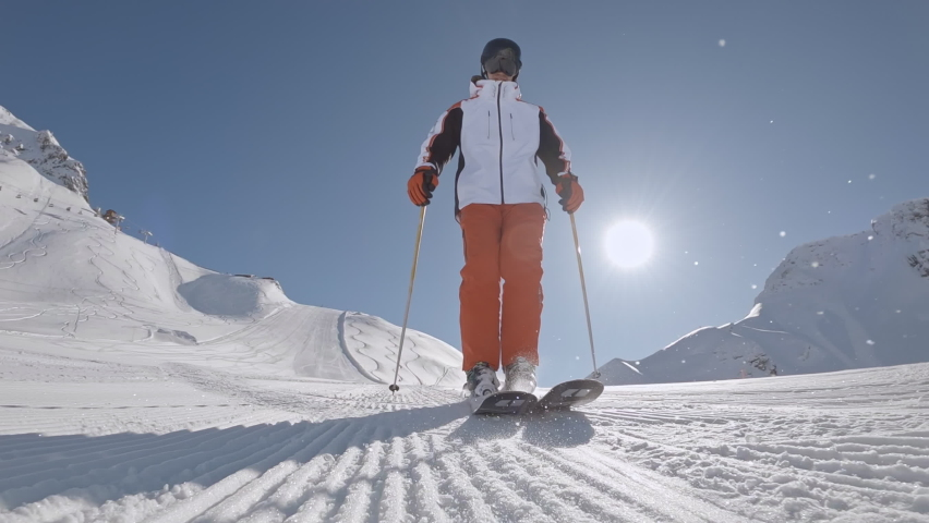 One Man downhill skier slowly down the ideal ski slope. Skiing on the track against the backdrop of picturesque snow-capped mountains. Winter outdoor activities. Slow motion, 2K RAW footage, 2704x1520 | Shutterstock HD Video #1059012599