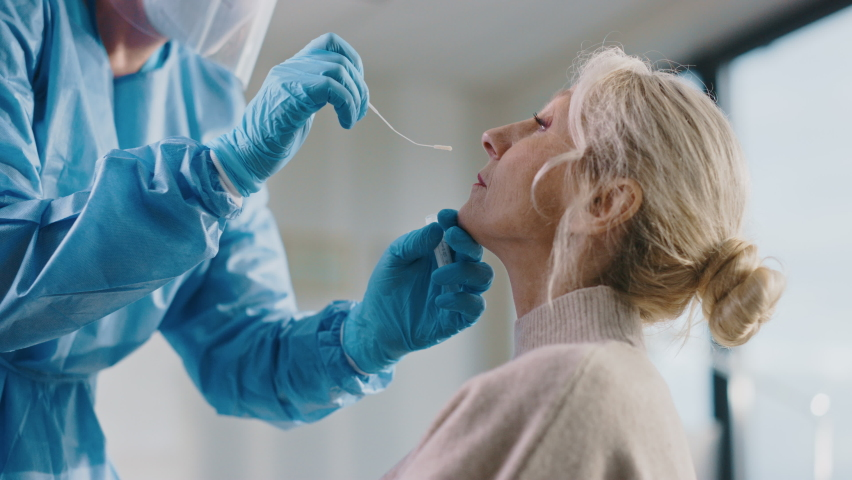 Medical Nurse in Safety Gloves and Mask, Protective Face Shield and Overalls is Taking a PCR Corona Virus Sample in a Health Clinic. Doctor Uses Respiratory Swab Test. Covid-19 Pandemic Concept. Royalty-Free Stock Footage #1059016376