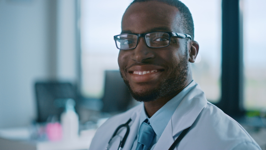 Close Up Portrait of African American Family Medical Doctor in Glasses is in Health Clinic. Successful Black Physician in White Lab Coat Looks at the Camera and Smiles in Hospital Office. Royalty-Free Stock Footage #1059016439