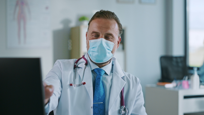 Family Doctor in Protective Mask is Reading Medical History of Young Male Patient and Speaking with Him During Consultation in a Health Clinic. Physician in Lab in Front of Computer in Hospital Office | Shutterstock HD Video #1059016541